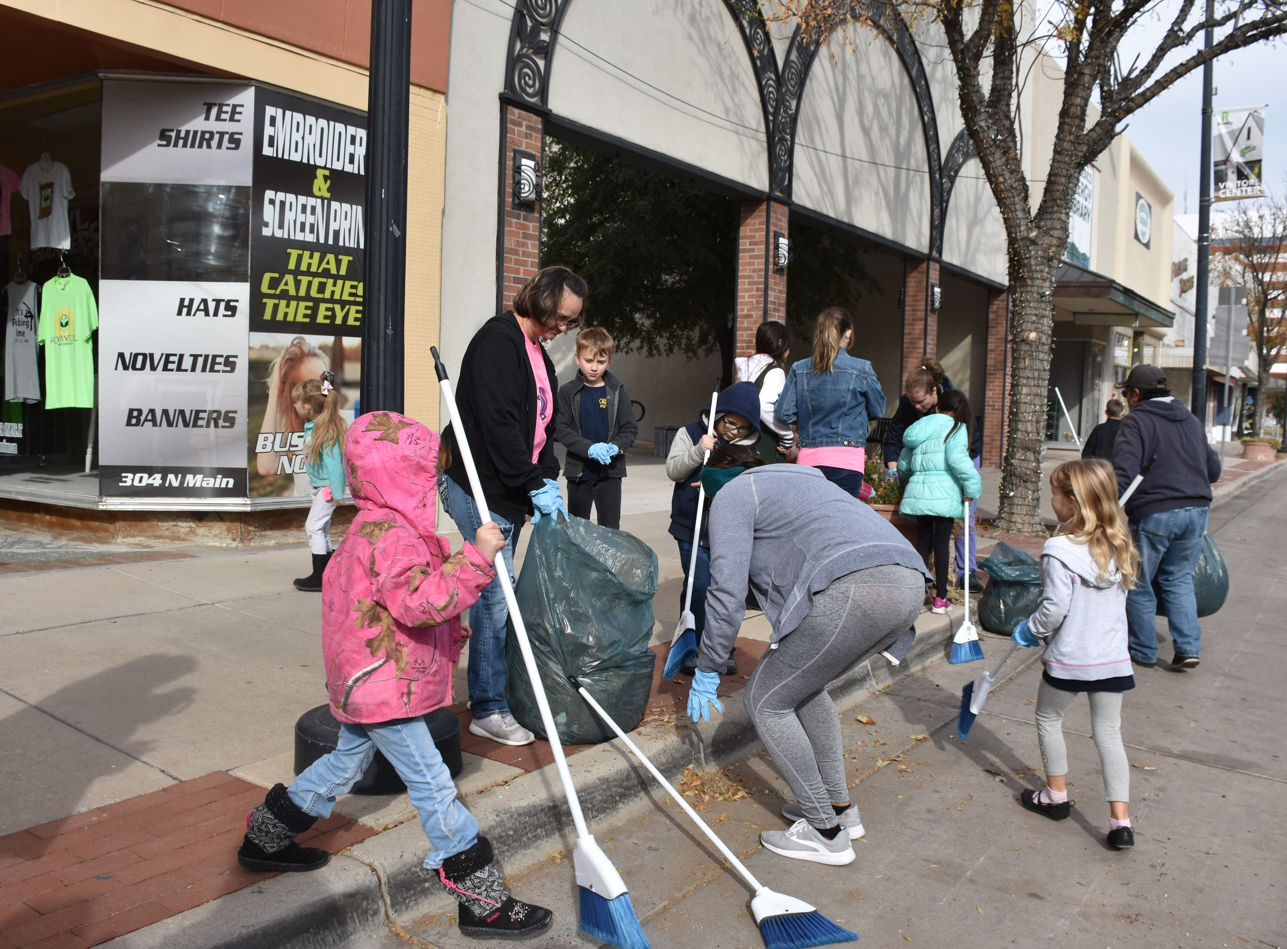 Volunteers cleaning  storefront in downtown