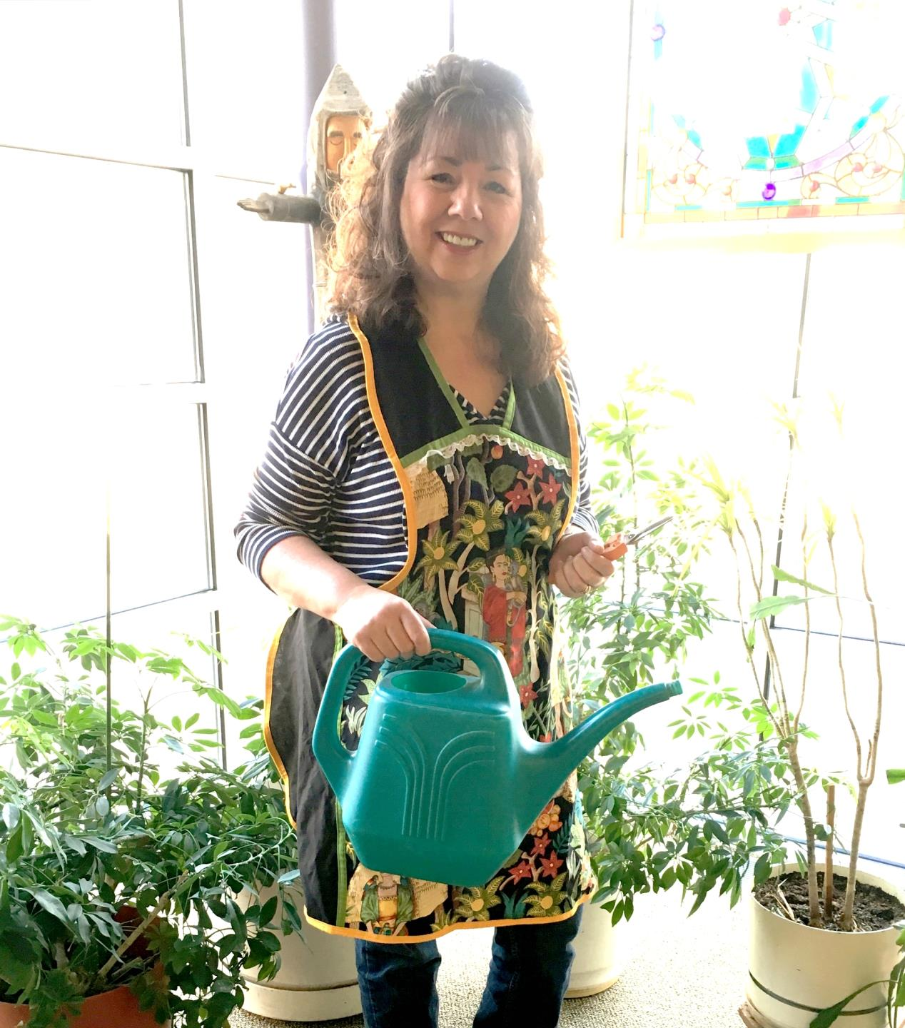 Library volunteer smiling while watering plants in the Childrens section